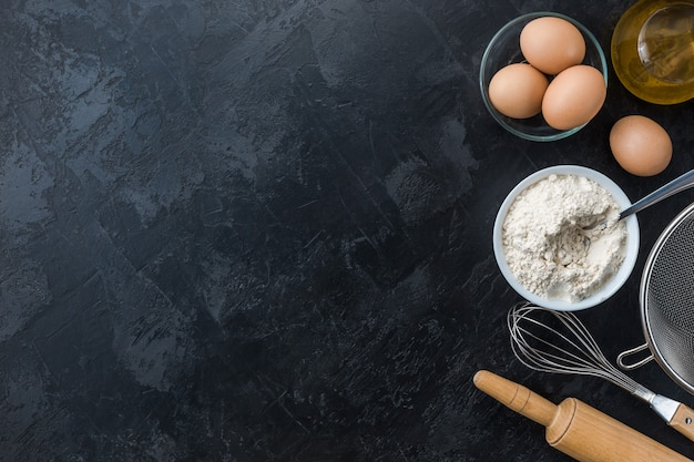 Bakken koken ingrediënten op zwarte achtergrond. bovenaanzicht. frame kopie ruimte.