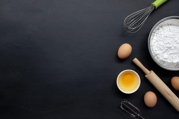 Bakken koken ingrediënten op zwarte achtergrond. bovenaanzicht