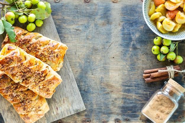 Bakken met appel, vers gebakken appel en kaneelbroodjes gemaakt van bladerdeeg op een witte houten tafel. bovenaanzicht, rustieke stijl, kopie ruimte.