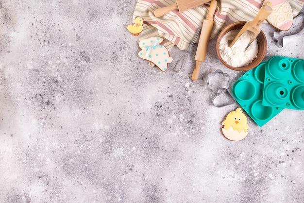 Bakkende toebehoren op steenachtergrond met bloem en pasen verglaasde koekjes