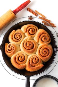 Bakkende verse verse gebakken eigengemaakte kaneelbroodjes van het voedselconcept in de pan van de koekepanijzer