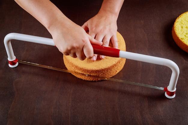 Bakker die de bovenkant van de cake snijdt met een gekartelde nivelleercake. een laagcake maken.
