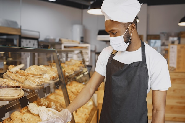 Bakker in uniform geeft advies over gebak. man met beschermend masker. vers brood kopen.