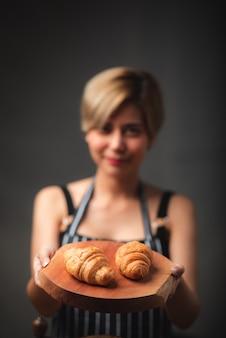 Bakker presenteert vers gebakken croissants in café dat gemaakt van bladerdeeg op zoek lekker, frans bakkerij concept.