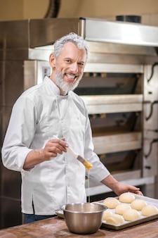 Bakker. tevreden man in uniform met borstel en kom in de buurt van broodje lade staande koken in bakkerij