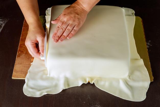 Bakker versiert vierkante taart met witte fondant
