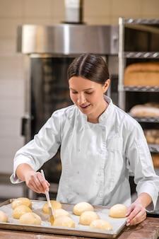 Bakker. vrolijke vrouw jonge volwassene in uniform met borstel in de buurt van broodje lade staande koken in bakkerij