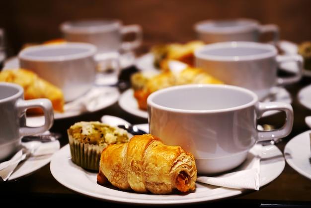 Bakkerij en drank op witte kop en schotel voor koffiepauzetijd.