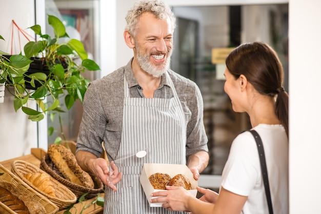 Bakkerij. gelukkige grijze haired verkoper die ingepakte broodjes toont aan vrouw met lang donker haar die zich met rug naar camera bevinden