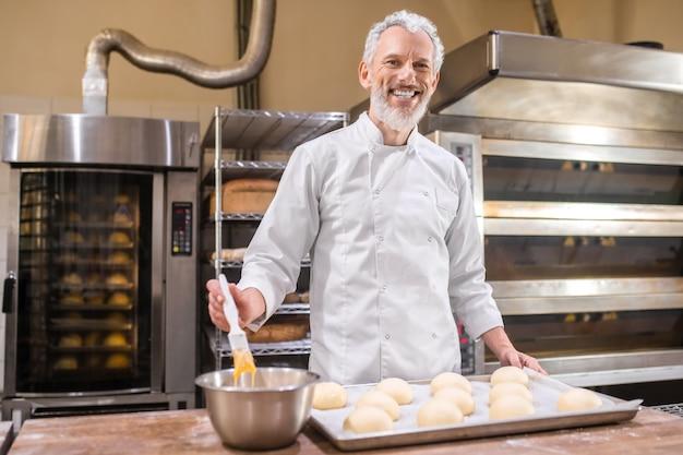 Bakkerij. glimlachende volwassen grijsharige bebaarde man in wit uniform broodjes voorbereiden bakken staande in de buurt van tafel