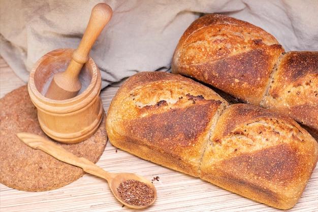 Bakkerij - gouden rustieke broodkorstjes. vers aromatisch brood op tafel. voedsel concept. houten lepel met lijnzaad.
