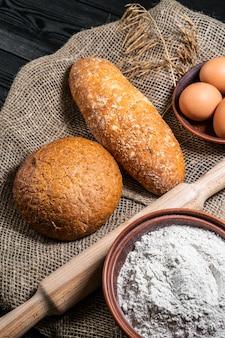 Bakkerij - gouden rustieke knapperige broden en broodjes op zwarte bordachtergrond.