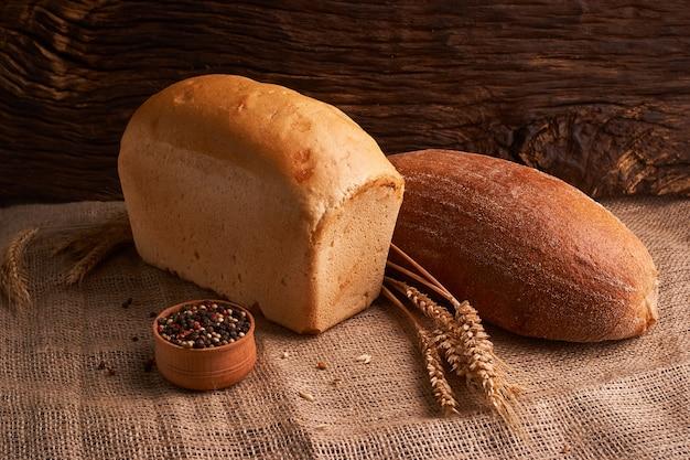 Bakkerij - gouden rustieke knapperige broden en broodjes op zwarte bordachtergrond