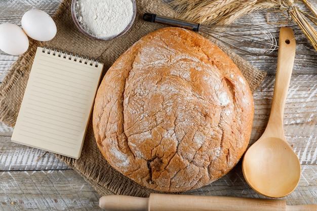 Bakkerij product met eieren, deegroller, kladblok, lepel, meel bovenaanzicht op een houten oppervlak