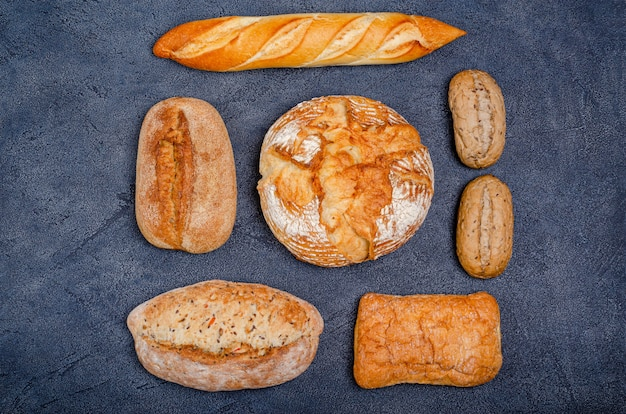 Bakkerij - verschillende rustieke knapperige broodjes met brood en broodjes op een donkere achtergrond.