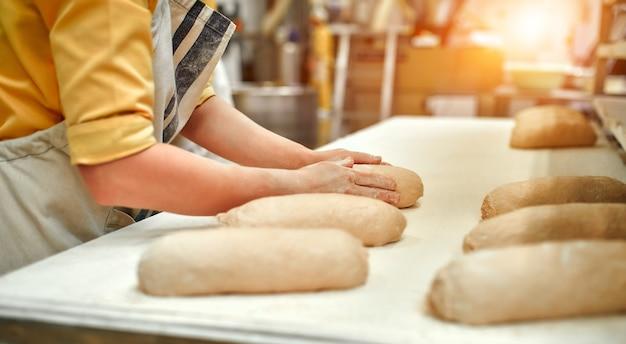 Bakkerij-voedselfabriek, productie van vers voedsel. de bakker staat aan de werktafel en maakt brood.