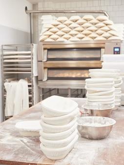 Bakkerij werktafel voor het kneden van brood met gestapelde broodpannen en meelbakken ovens
