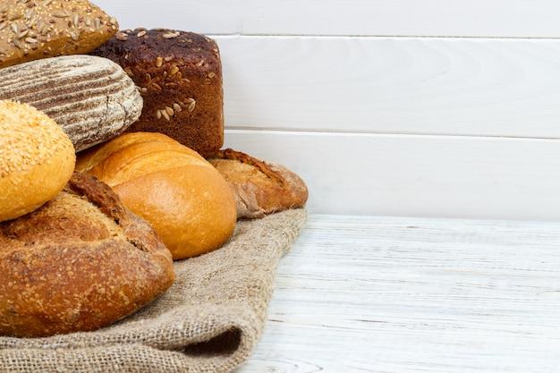 Bakkerijachtergrond, broodassortiment. roggebroodjes en frans baguettes bovenaanzicht