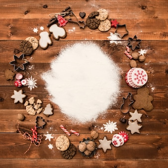 Bakkerijachtergrond met ingrediënten om te koken, verfraaide kerstmispeperkoek. poedersuiker, kopie ruimte, bovenaanzicht