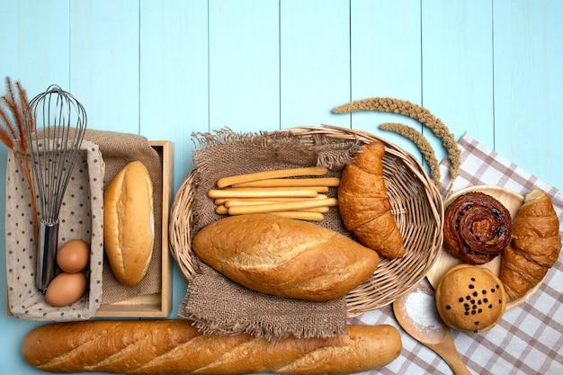 Bakkerijbrood op blauwe houten lijst. verschillende soorten brood en schoof van tarwe.