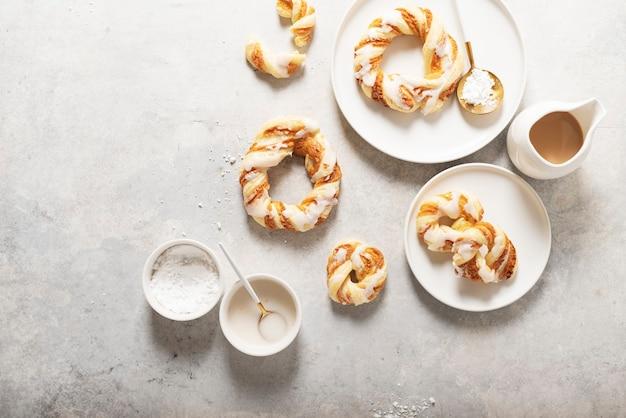 Bakkerijconcept, zoete ronde desserts met geglazuurde suiker op het lichte oppervlak. bovenaanzicht.