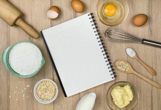 Bakkerijhulpmiddelen en notitieboekje op hout