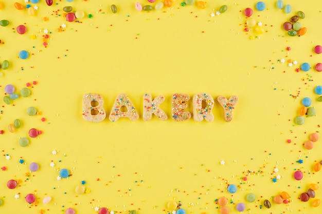 Bakkerijinscriptie gemaakt van zoete suikerkoekjes en versierd met prachtige regenbooghagelslag, uitzicht van bovenaf