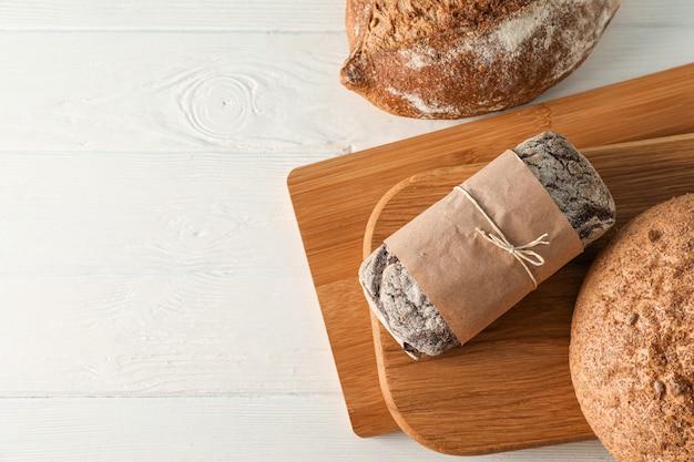 Bakkerijproducten en snijplanken op witte houten ruimte, bovenaanzicht en ruimte voor tekst