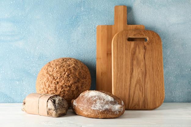 Bakkerijproducten en snijplanken op witte houten tafel tegen lichte ruimte, ruimte voor tekst