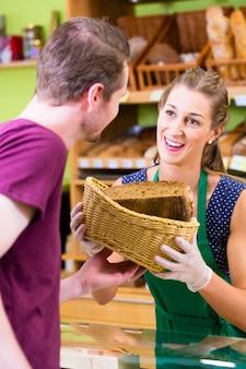 Bakkerijverkoopster die brood aanbiedt