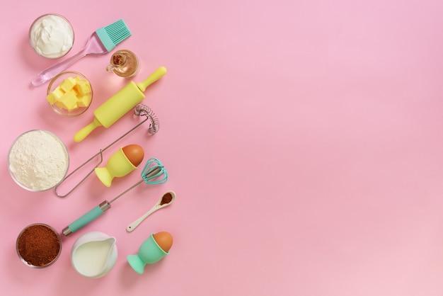 Bakkerijvoedselkader, het koken concept. ingrediënten op keukentafel. boter, suiker, meel, eieren, olie, lepel, deegrol, borstel, klop op roze achtergrond.