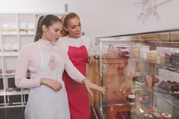 Bakkers bekijken het winkeldisplay in hun rauwe veganistische zoetwarenwinkel