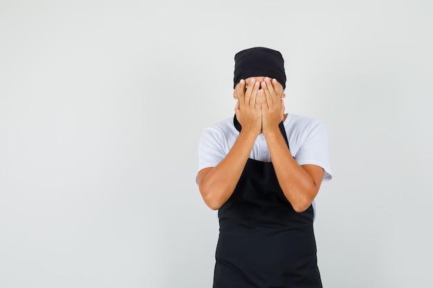 Bakkersman in t-shirt, schort die gezicht bedekt met handen en weemoedig kijkt