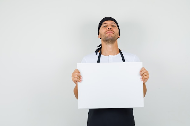 Bakkersman in t-shirt, schort die leeg canvas vasthoudt en trots kijkt