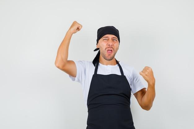 Bakkersman in t-shirt, schort die winnaargebaar toont en gelukkig kijkt