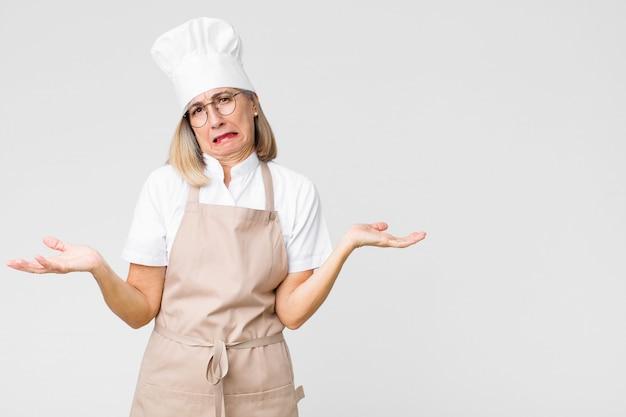 Bakkersvrouw van middelbare leeftijd kijkt verbaasd, verward en gestrest, vraagt zich af tussen verschillende opties, voelt zich onzeker tegen een vlakke muur