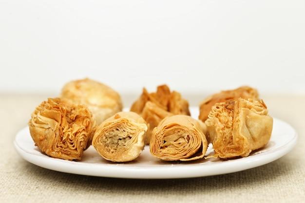 Baklava gemaakt van dun deeg met gehakte noten en honing siroop op de tafel op een lichte achtergrond. selectieve aandacht. kopieer ruimte.