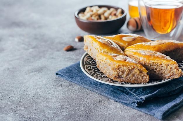 Baklava. ramadan dessert. arabisch dessert met noten en honing, kopje thee op een concrete achtergrond.