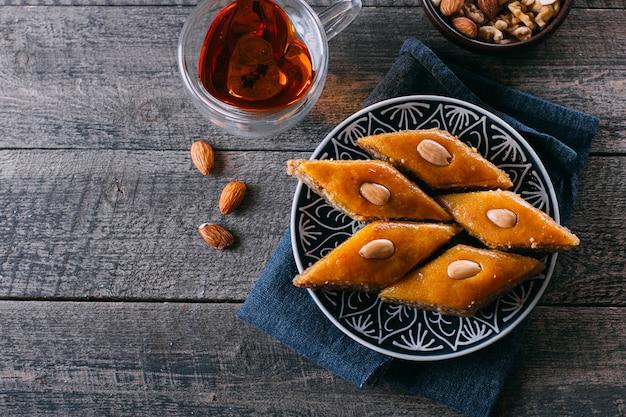 Baklava. ramadan dessert. arabisch dessert met noten en honing, kopje thee op een houten achtergrond.