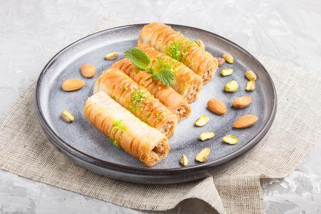 Baklava, traditionele arabische snoepjes in grijze ceramische plaat dicht omhoog.