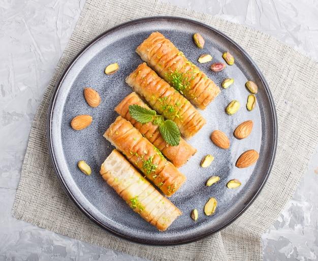 Baklava, traditionele arabische snoepjes in grijze keramische plaat op een grijs beton. bovenaanzicht.