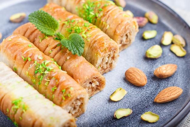 Baklava, traditionele arabische snoepjes in grijze keramische plaat op een grijze concrete achtergrond.