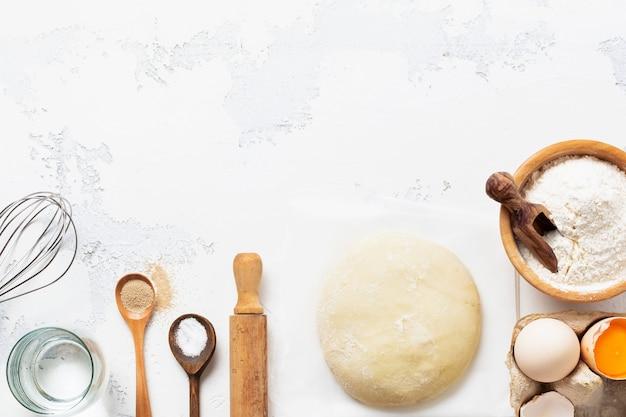 Bakmuur met deeg en ingrediënten voor de bereiding van deegwaren of pannenkoeken, eieren, bloem, water en zout op witte rustieke oude lijst. bovenaanzicht.