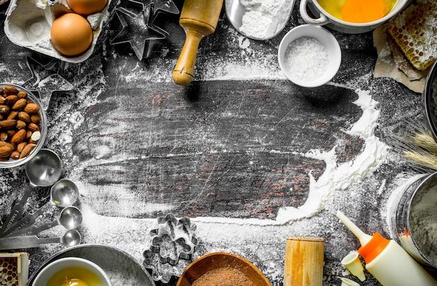 Bakoppervlak. diverse ingrediënten voor het koken van zelfgemaakte koekjes. op rustieke ondergrond met bloem