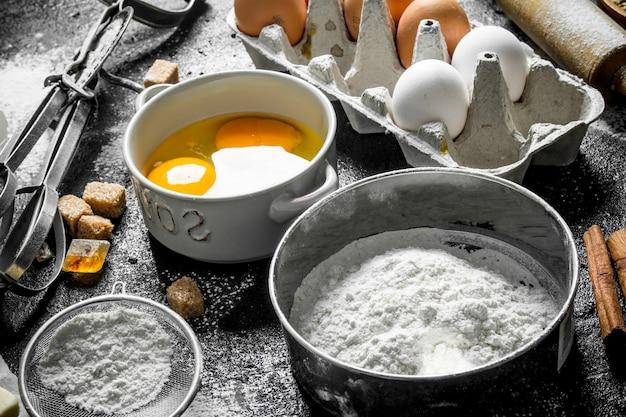 Bakoppervlak. ingrediënten om thuis koekjes te maken. op zwarte rustieke ondergrond