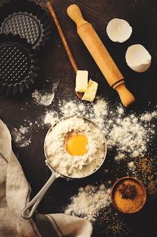 Bakoppervlak met ingrediënten meel, eieren, suiker, boter, kaneel, anijs ster en keukengerei op donkere oude rustieke tafel. selectieve aandacht. getinte afbeelding. bovenaanzicht.