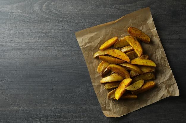 Bakpapier met aardappelpartjes op donkere textuur