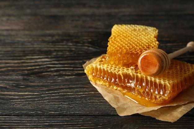 Bakpapier met honingraatstukken en beer op houten achtergrond