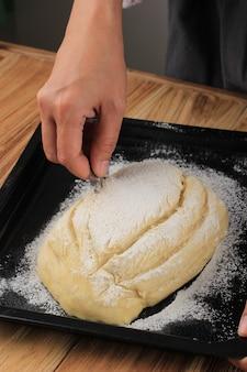 Bakproces: brood maken, rauw rond japans brooddeeg uit de oven maken. vrouwelijke hand die een kruissnede op de bovenkant van het deeg maakt met scheermes