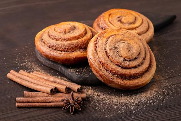 Baksamenstelling zelfgemaakte broodje op snijplank anijs ster en kaneelstokjes in de buurt van hen